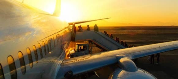 Passengers Boarding Plane at Sunset on Tarmac