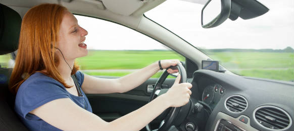 an attractive young woman driving a car in a careless manner listening to music