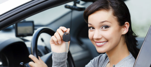 young woman showing off her car rental keys