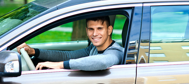 smiling guy inside his rental car ready to drive