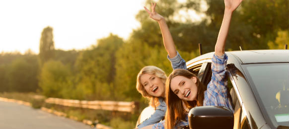 cheerful girls sitting in their rental car for vacation