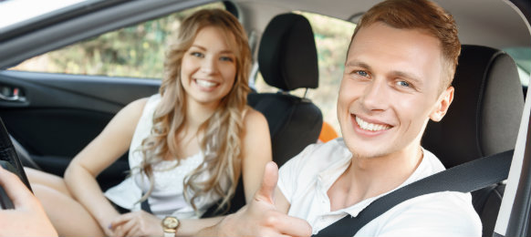 A man giving a thumbs up while beside her girlfriend in the car
