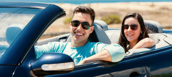 couple inside a blue convertible car rental