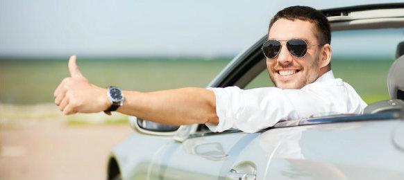 dapper guy posing at camera inside his car