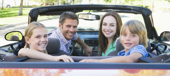 happy family in convertible car smilin