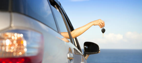 hand of woman holding her car rental key