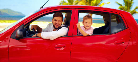happy father and son traveling a car rental on summer vacation