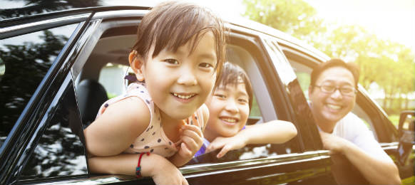 happy little girl with her family in a car rental for vacation
