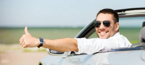 happy man driving cabriolet car rental and showing thumbs up