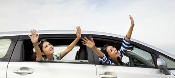 happy girls in their car rental and enjoying vacation