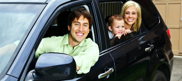 happy young family sitting in black car rental looking out windows