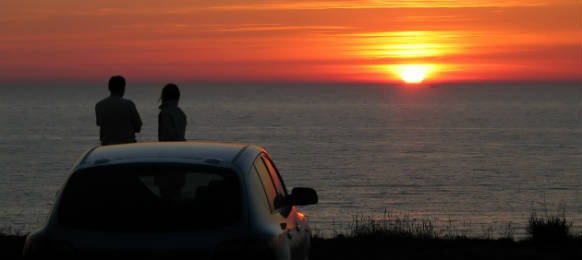 man and woman standing beside their car rental watching a sunset