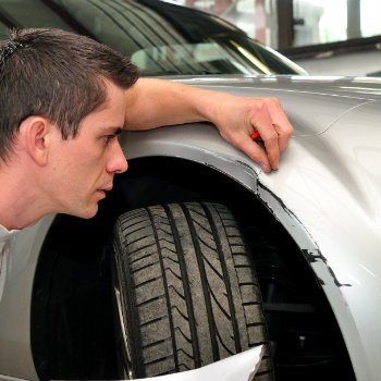 Man checking a additonal damage in his car rental vehicle