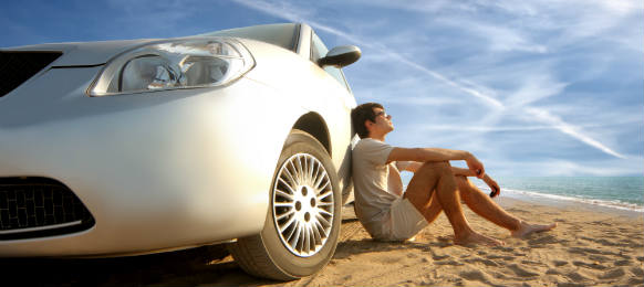 man sitting behind his white car rental staring at the sky in a brown sand