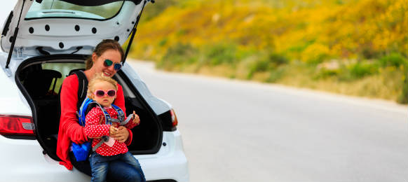 mother and little daughter travel by car in summer nature