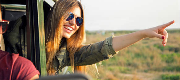outdoor portrait of beautiful girl on her car rental roadtrip pointing forward