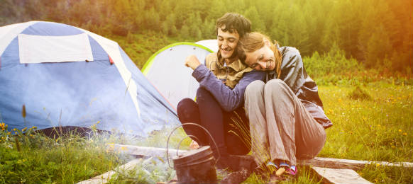 portrait of happy couple sitting near by the campfire with the tents