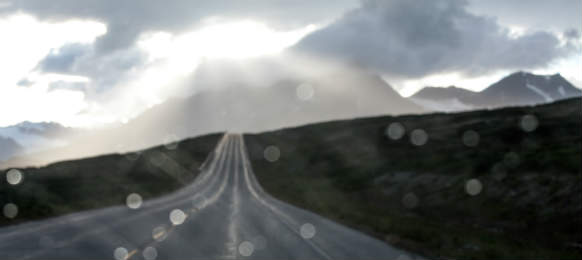 rain on a car windshield on a lonely mountain highway with storm clouds
