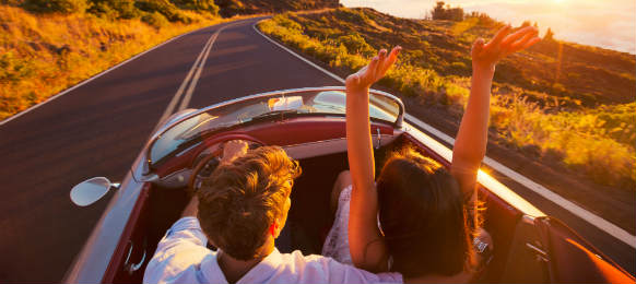 Driving a car rental into the sunset romantic young couple enjoying sunset drive