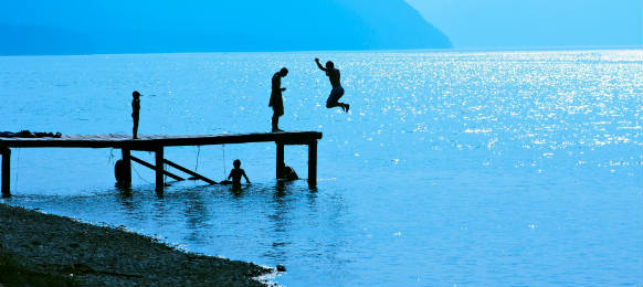 silhouettes of kids who jump off dock on the lake blue toned