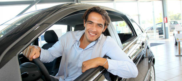 smiling man sitting at the steering wheel of his car rental