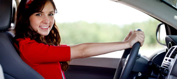 smiling woman driving the car rental