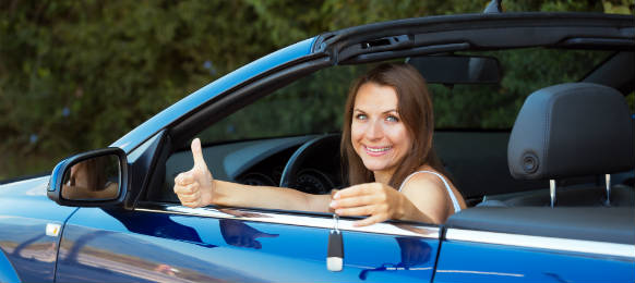 smiling caucasian woman key in a her blue car rental