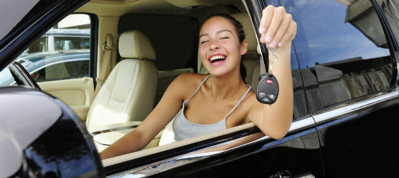 smiling woman showing keys of her expensive car rental