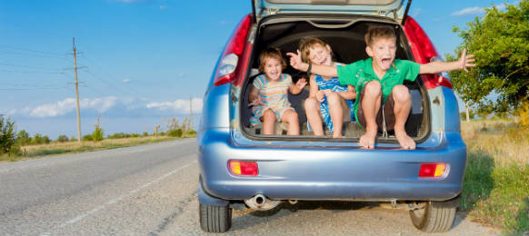 three happy kids in a car rental ready for summer vacation travel