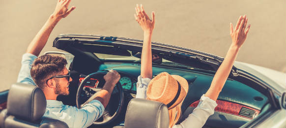 top view of cheerful young couple keeping arms raised while riding in their white convertible