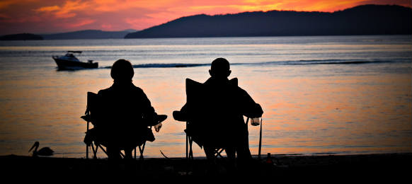 two friends silouhette straing at the sunset in the bay