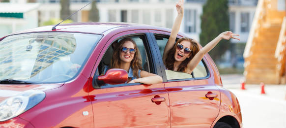 two happy girlfriends traveling with their car rental