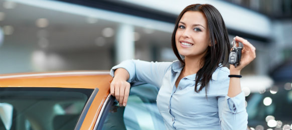 Woman beside her orange car holding a car key