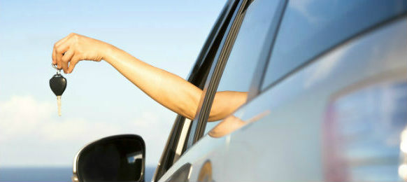 woman holding key outside the left side of a car rental