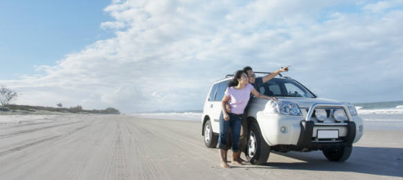 young couple is enjoying her honeymoon at the beach beside a car