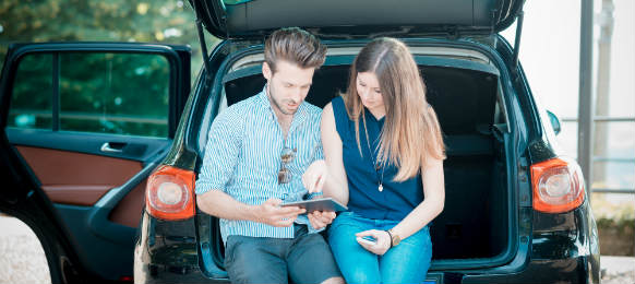 young couple using tablet sitting in their car