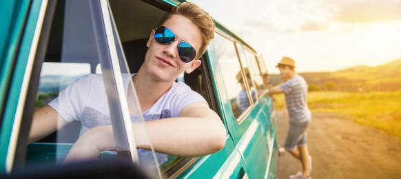 young hipster friends rent a car on road trip on a summer day