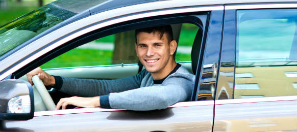 young man at driver seat of his car rental looking through window