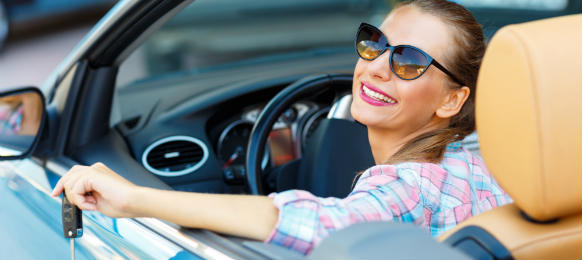 young pretty woman in sunglasses sitting in a convertible car rental with the keys in hand