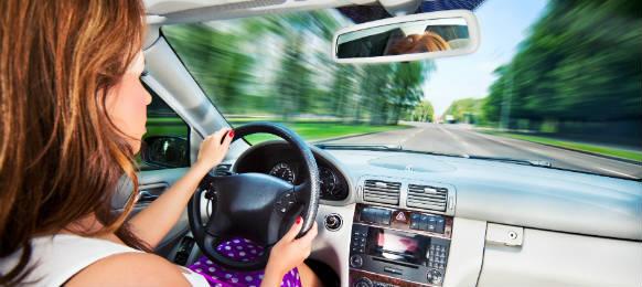 jeune femme au volant de sa location de voiture dans un effet de mouvement rapide