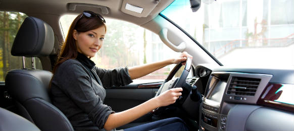 young woman driving the car rental