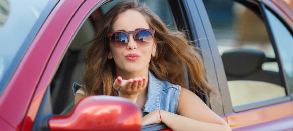 young woman giving a flying kiss through her car rental window